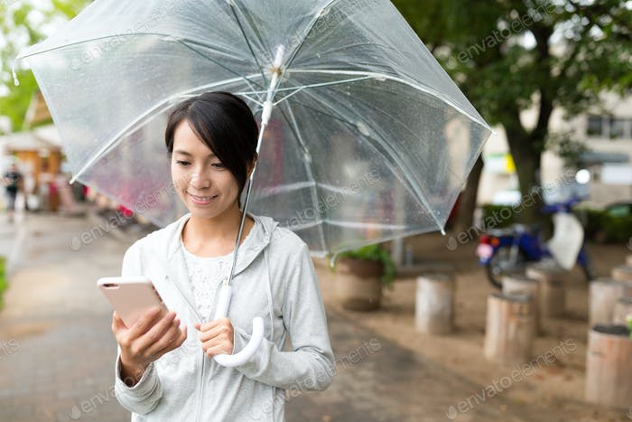 Woman use of mobile phone in rainy day