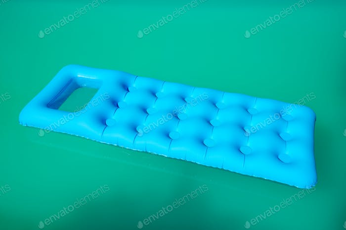 Inflatable mattress floating on swimming pool surface