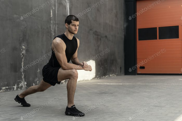 Handsome, athletic man warming up stretching before the training