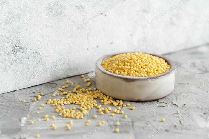 Raw dry hulled millet in a ceramic bowl