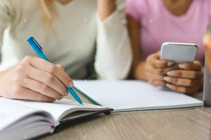 Teen girl writing notes in notebook, studying with friends outdoor