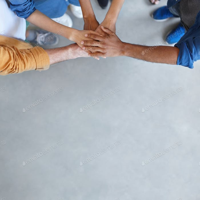 Horizontal portrait of group of people standing together stacking their hands showing their unity. Y