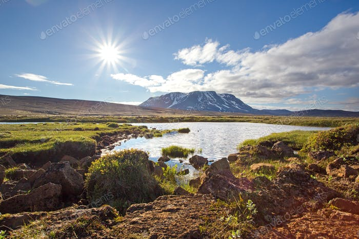 Icelandic summer nature scenery with sun, lake and mountain