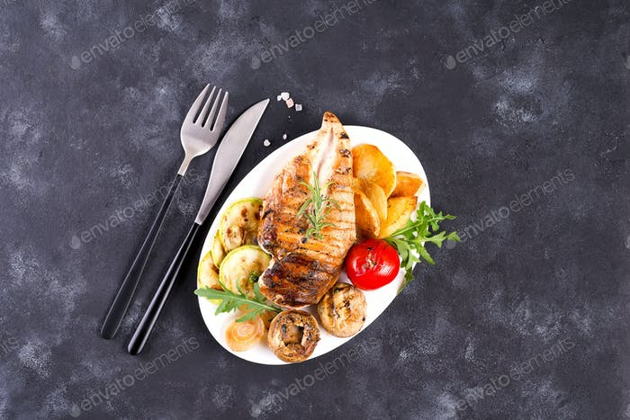 Chicken breast grill with bbq vegetables and pesto sauce in a plate on a concrete background, flat