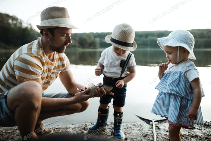 A mature father with small toddler children fishing by a lake, holding a fish.