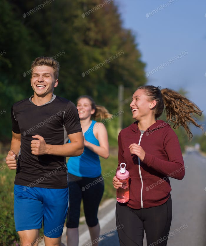 young people jogging on country road