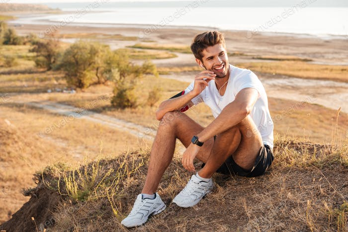 Young sportsman resting and listening music with earphones after workout