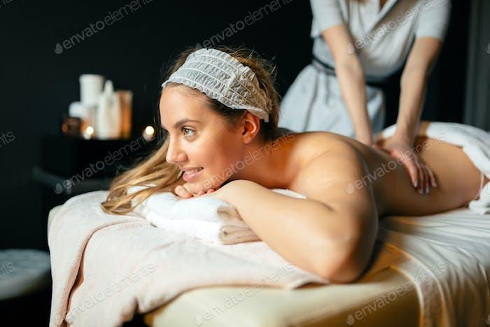 Beautiful young and cute woman enjoying massage treatment