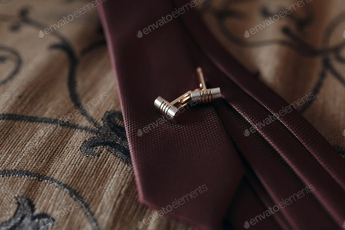 stylish golden cufflinks on red tie on bed. morning preparation for wedding. groom getting ready.