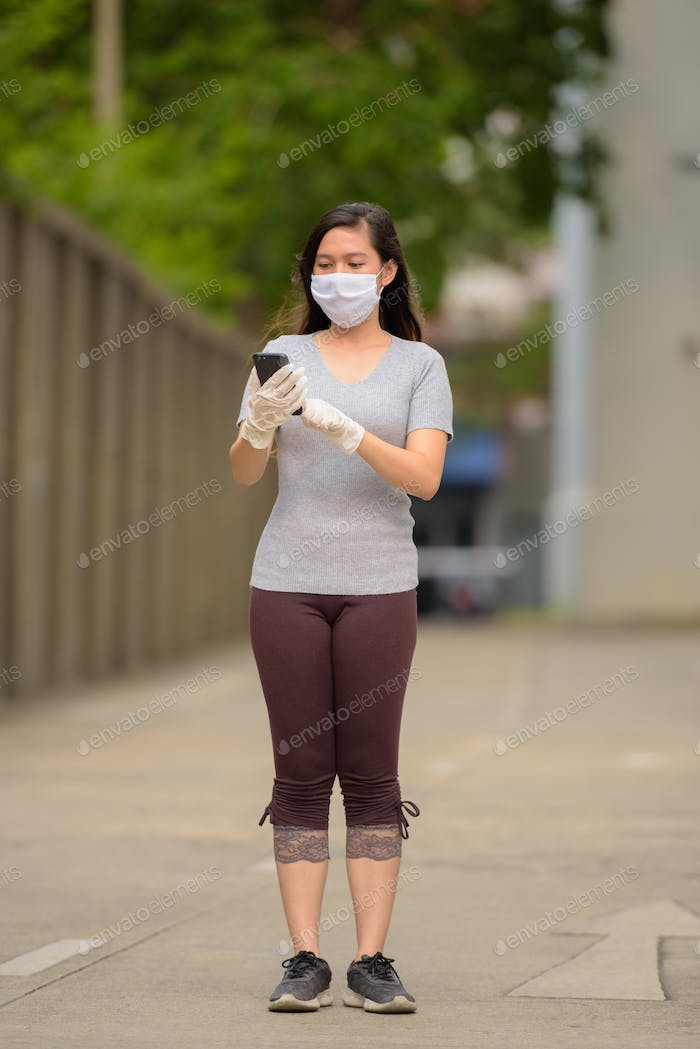 Full body shot of young Asian woman wearing mask and gloves while using phone outdoors