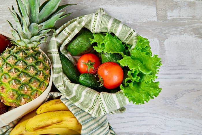 Fresh vegetables and fruits in eco cotton bags on table in the kitchen.