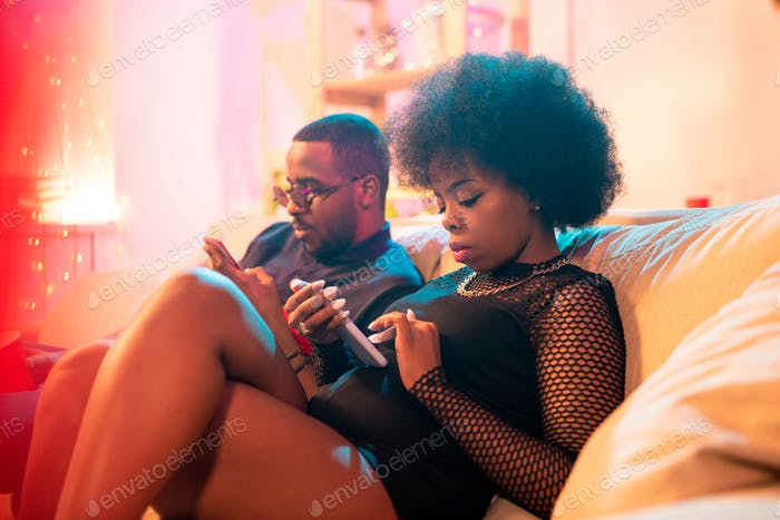 Two young serious millennials of African ethnicity texting in smartphones