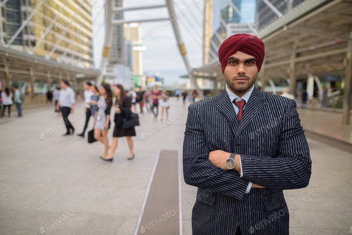 Indian businessman with turban outdoors in city with arms crossed