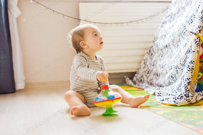 Cute baby boy toddler playing with toy indoors