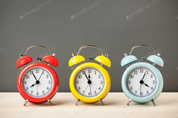 Three colorful alarm clocks on desktop