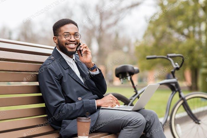 Handsome businessman having business talk during break in park