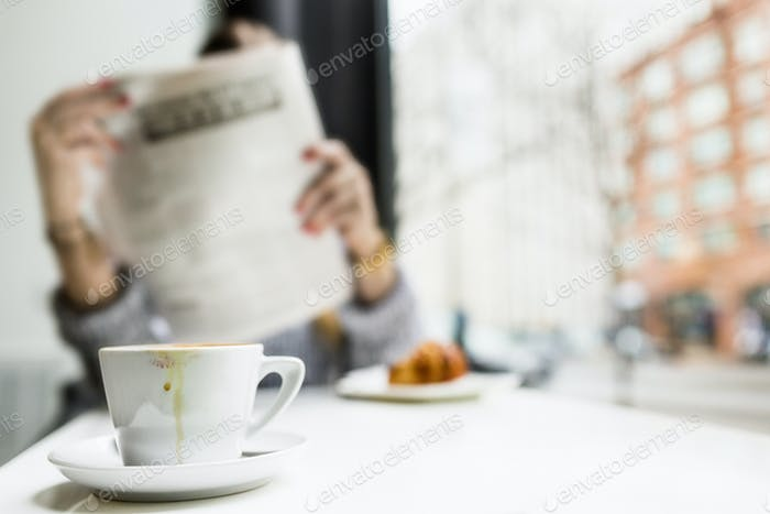 Woman reading newspaper while having breakfast at coffee shop