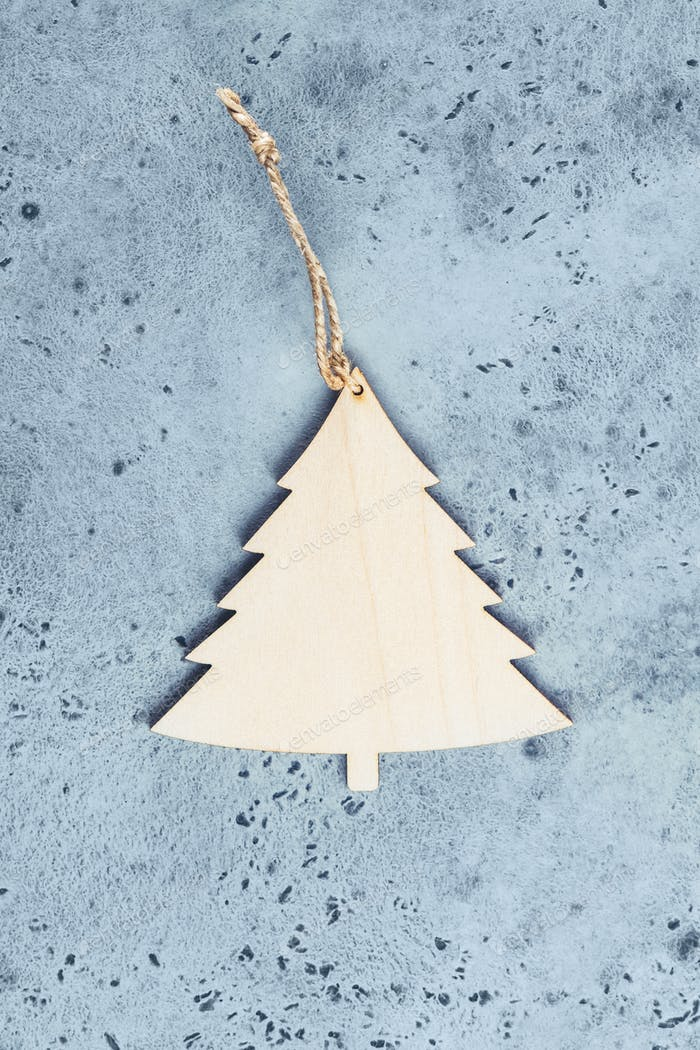 Wooden Christmas decor in spruce's shape on a blue background. Top view, flat lay.