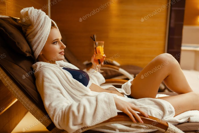 Sexy girl relaxing with cocktail in spa chair