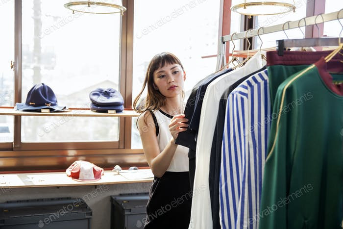 Japanese saleswoman standing in clothing store, looking at shirt.