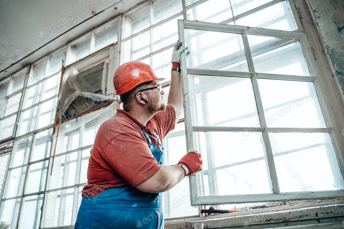 Fat builder working with a window at a big construction site