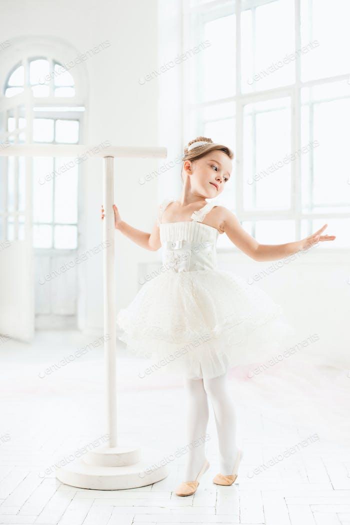 Little ballerina girl in a tutu. Adorable child dancing classical ballet in a white studio.