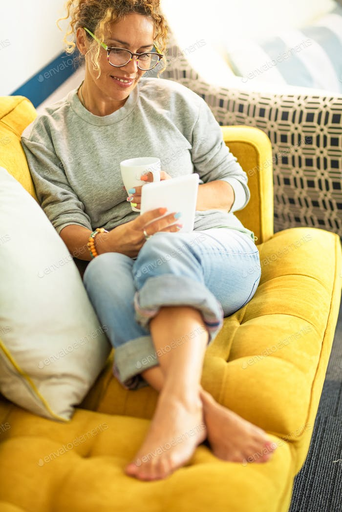 Happy adult female enjoy relax time at home reading a digital book on modern device sitting