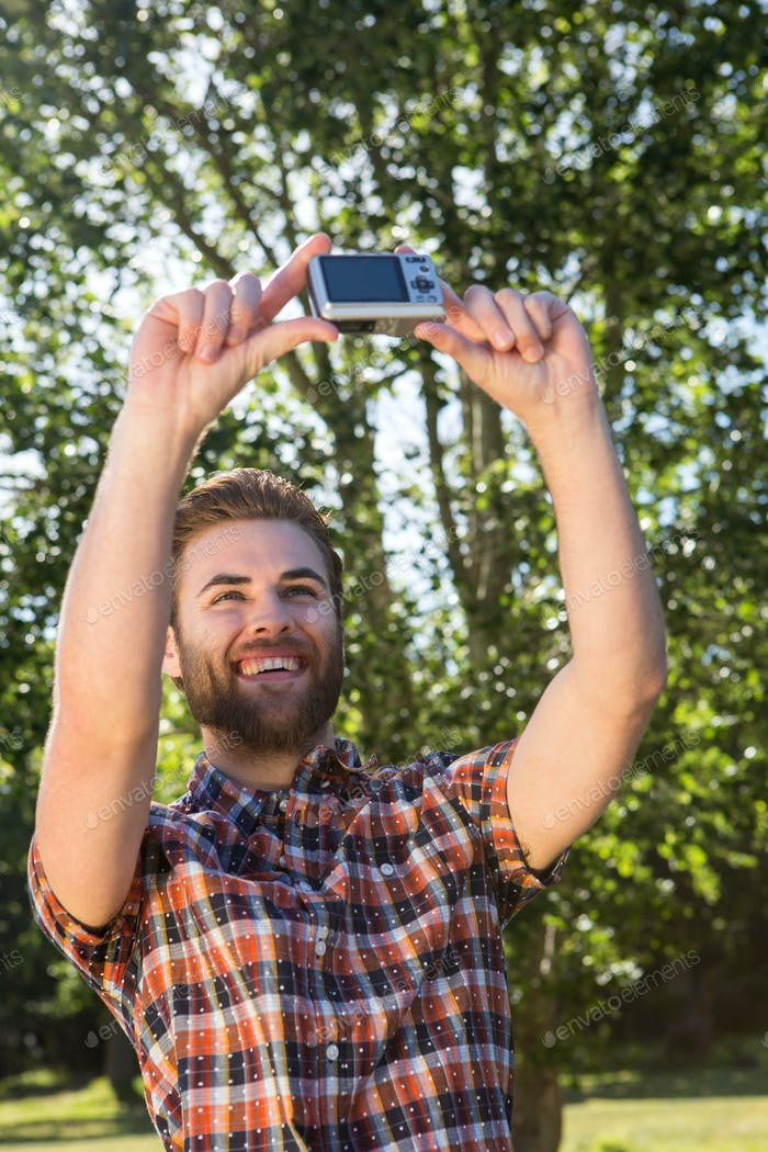 Handsome hipster taking a selfie on a summers day