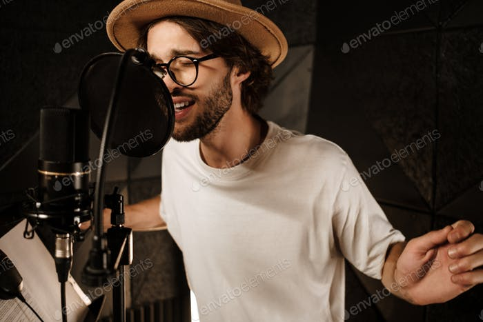 Handsome stylish male musician emotionally singing in microphone recording song in studio