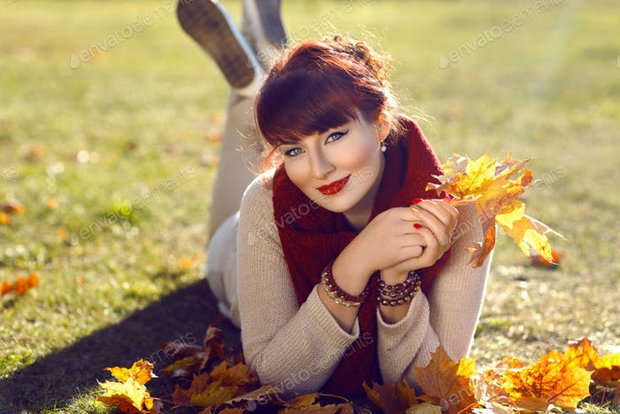Girl lying on ground with yellow leaves