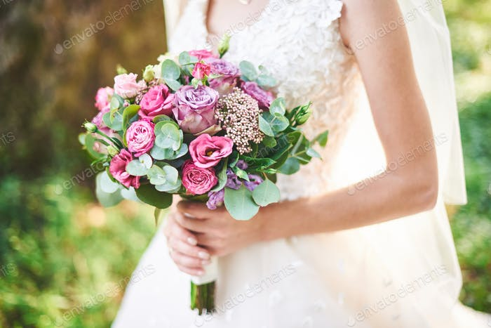 bride in a white dress holding a bouquet of purple flowers and greenery