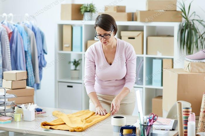 Junge lässige weibliche Biegung über Schreibtisch während Falten Baumwolle Pullover