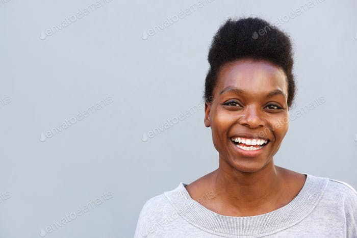 Cheerful african female standing against gray background