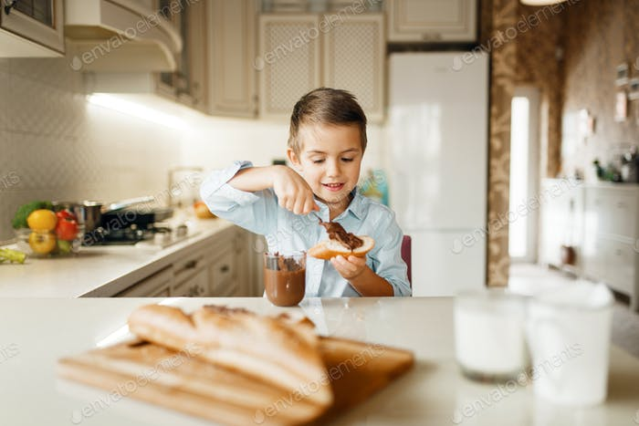 Young boy smears melted chocolate on bread