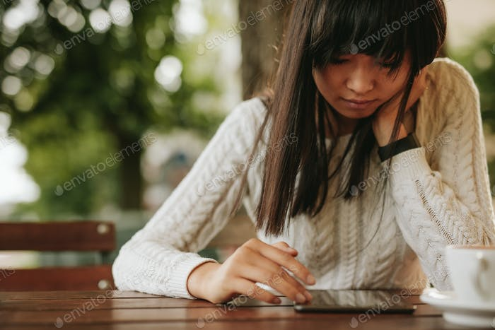 Young woman using digital tablet at coffeeshop