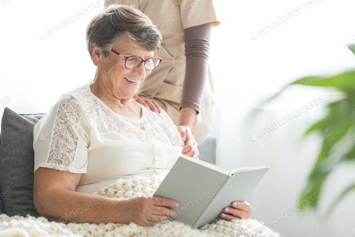 Smiling senior patient reading book
