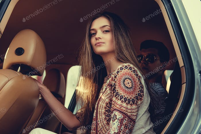 Female with long hair sitting in a car.