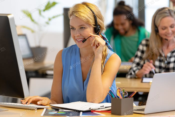 Happy Caucasian female customer service executive talking on headset and working on computer