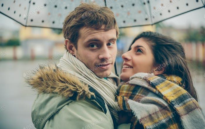 Feliz pareja abrazando al aire libre bajo el paraguas en días lluviosos