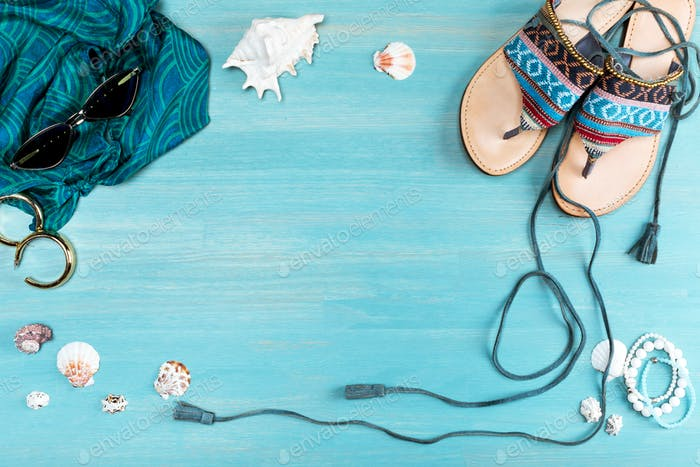 top view of sunglasses, scarf, sandals and sea shells on table