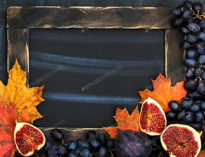 Autumn frame with chalk board, leaves, figs and grape,  space fo
