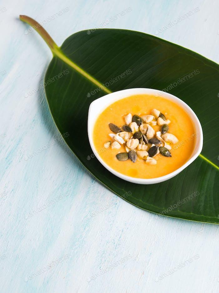 Kürbiscremige Suppe serviert auf grünem Blatt