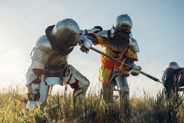 Medieval knights fight with sword and axe