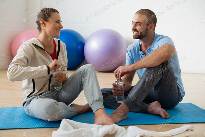 Instructor and student talking while having water in yoga studio