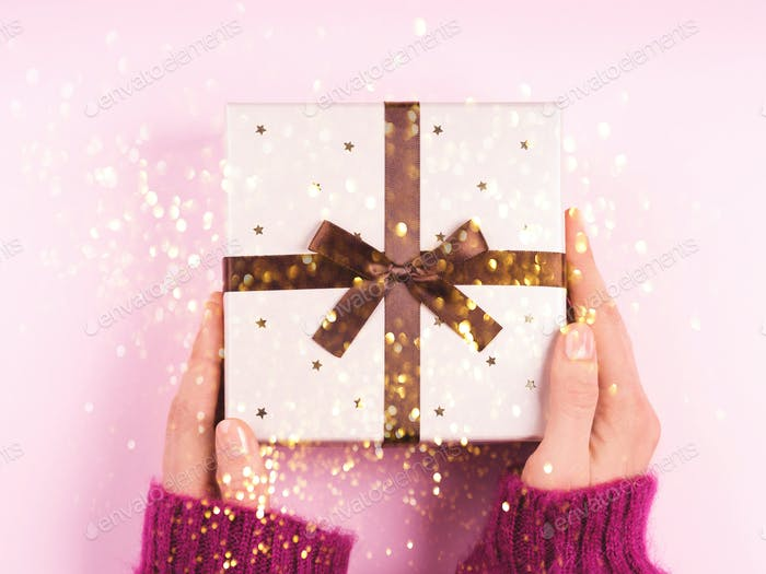 Woman's hands holding gift bow with bow
