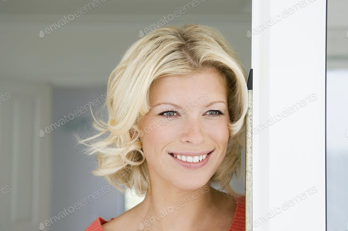 A young women with blonde hair smiling in a doorway.