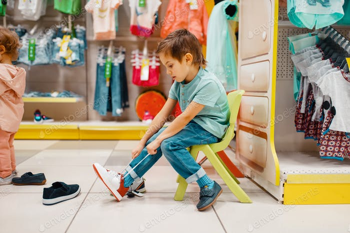 Little boy trying on shoes in kids store
