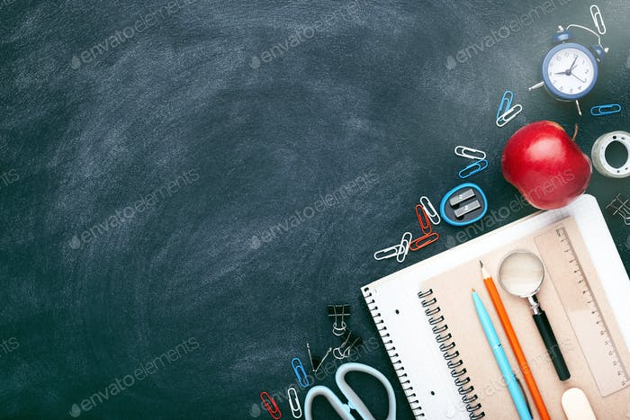 Schulstationär: Stift, Bleistifte, Notizbuch auf Tafel.