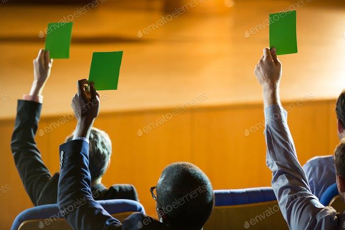 Rückansicht von Führungskräften zeigen ihre Zustimmung, indem sie Hände heben