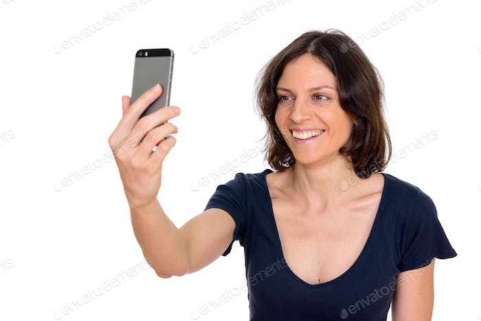 Studio shot of beautiful woman taking selfie isolated against white background